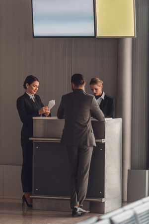 rear view of businessman standing at airport check in counter Zdjęcie Seryjne