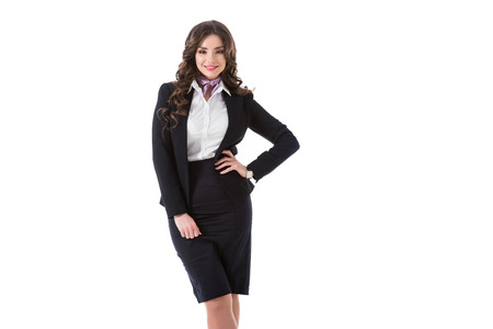 beautiful stewardess with arm akimbo looking at camera isolated on white