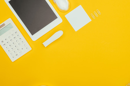 top view of digital tablet with blank screen, calculator and office supplies isolated on yellow 免版税图像 - 114249817