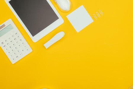 vue de dessus de la tablette numérique avec écran blanc, calculatrice et fournitures de bureau isolées sur jaune