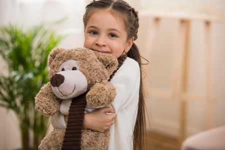 adorable little child hugging teddy bear and smiling at camera Stock Photo