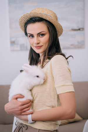 young stylish woman in hat holding cute white rabbit