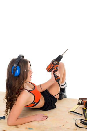 seductive girl in protective headphones posing with electric drill at wooden table with tools, isolated on white Stock Photo