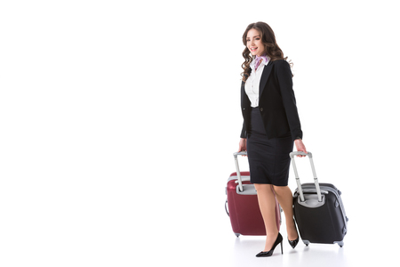 beautiful stewardess with bags on wheels isolated on white Foto de archivo