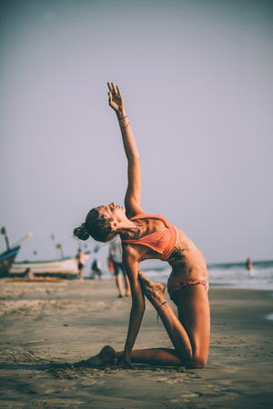 young flexible woman in swimsuit practicing yoga on sandy beach at goa Stock Photo