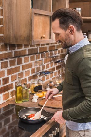handsome man stirring vegetables on frying pan