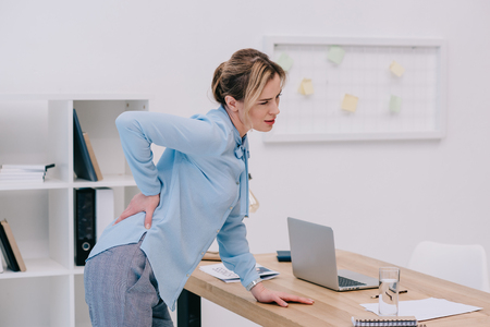 overworked adult businesswoman with backpain at office