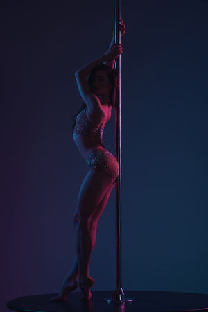 full length view of beautiful seductive young woman posing with pole on blue Standard-Bild - 114250056