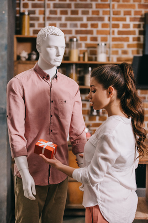 young woman pretending to except gift from mannikin, loneliness and perfect man dream concept Foto de archivo