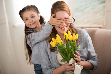 happy child closing eyes to cheerful mother holding yellow tulips