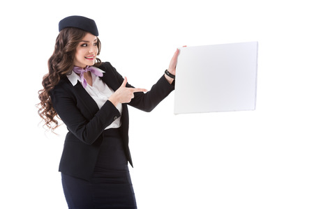 beautiful stewardess pointing on empty board isolated on white