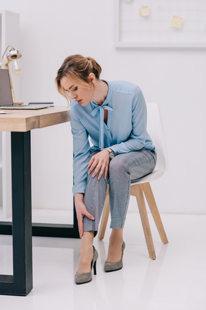 businesswoman with pain in ankle at workplace