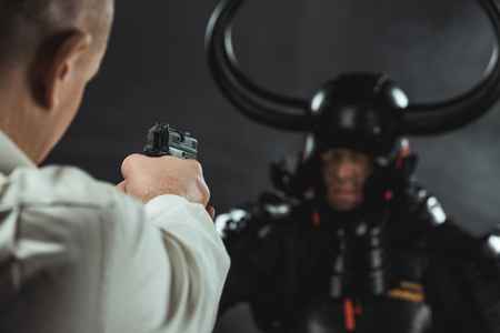 close-up shot of man aiming on armored samurai with gun Stok Fotoğraf