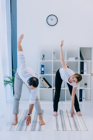 businessman with his trainer practicing yoga in triangle pose at office