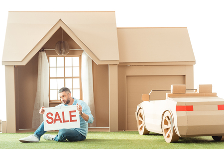 man holding sale signboard in front of cardboard house isolated on white Stockfoto