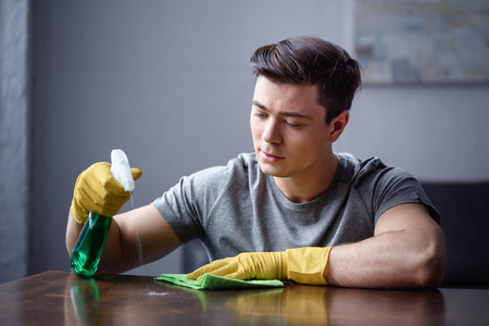 man cleaning table in living room with spray bottle and rag