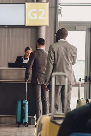 rear view of queue of businesspeople at airport check in counter Stockfoto