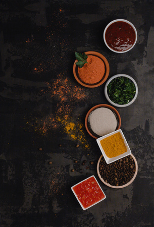 top view of various spices in bowls on dark concrete surface