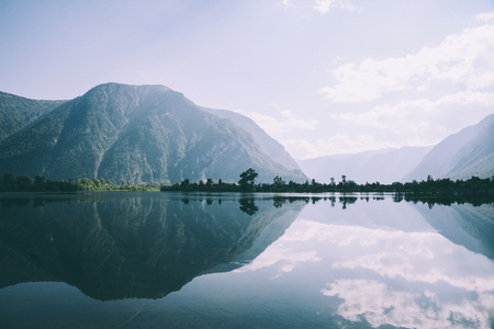 majestic mountains reflected in calm mountain lake in Altai, Russia Stock Photo