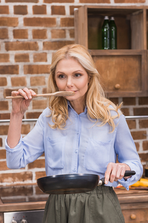 woman tasting food from wooden spatula