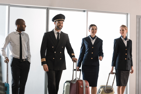 happy aviation personnel team walking by airport loggy with suitcases Stockfoto