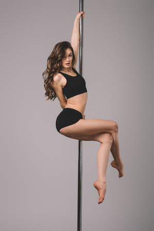 seductive young woman dancing with pole and looking at camera on grey