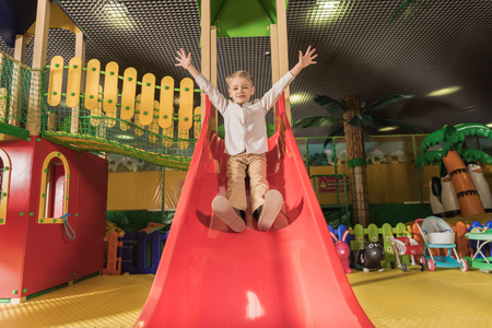 cute happy little boy with raised hands playing on slide in entertainment center Stockfoto