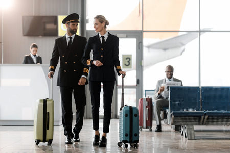 male and female pilots walking by airport lobby with suitcases