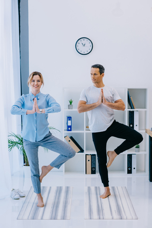 fit businesswoman with her trainer practicing yoga in tree pose at office Stock Photo
