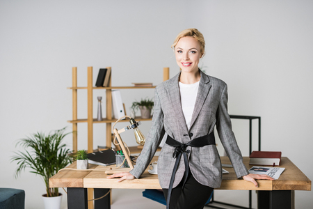 portrait of smiling businesswoman leaning on table in office Stock Photo