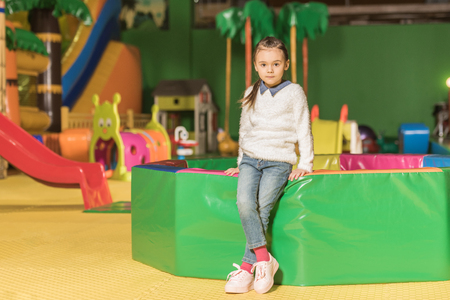 cute little child looking at camera while standing in entertainment center