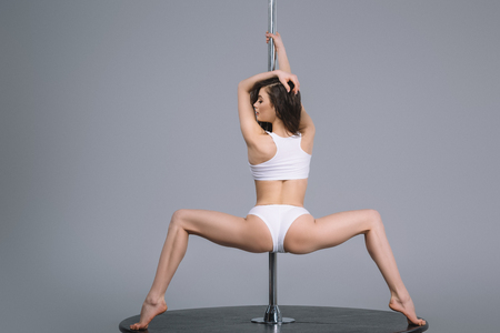 back view of young sporty woman in sportswear exercising with pole on grey