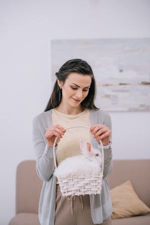 attractive young woman holding white rabbit in basket Stok Fotoğraf - 114250329