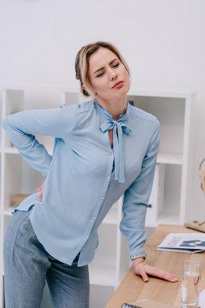 overworked adult businesswoman with backpain leaning on table at office