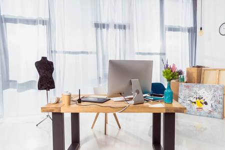 Work place of designer with tailor dummy and computer