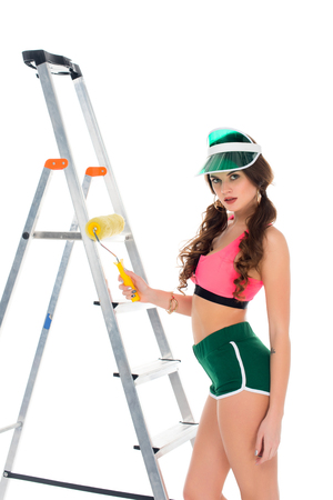 sexy girl in visor holding painting roller and standing near ladder, isolated on white Stock Photo