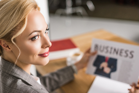 selective focus of businesswoman with newspaper at workplace Imagens