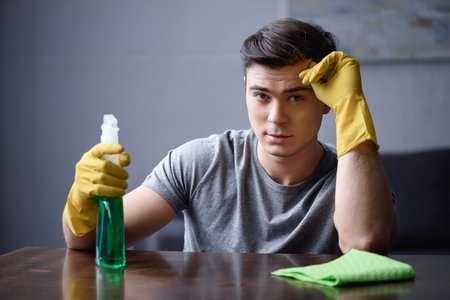 handsome man with spray bottle and rubber gloves looking at camera Stock Photo