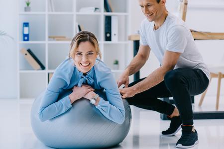 donna d'affari che lavora su fit ball con trainer in ufficio