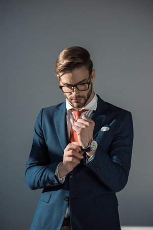 portrait of handsome young businessman wearing wristwatch isolated on grey