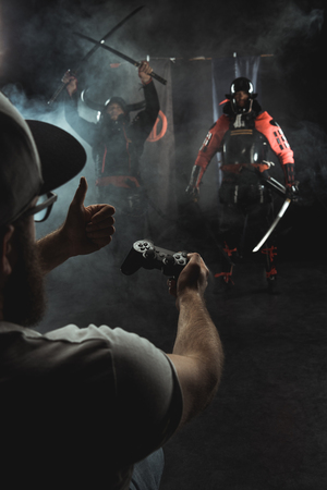 mature man playing samurai fighting with gamepad in real life and showing thumb up to characters Reklamní fotografie