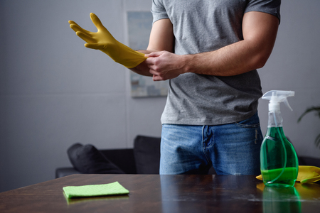 cropped image of man wearing rubber gloves for cleaning living room