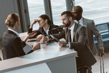 Grupo de empresarios enojados que tienen una discusión con la recepcionista del aeropuerto