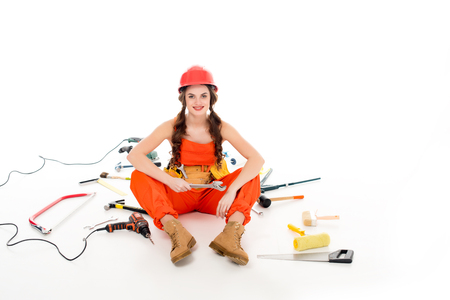 girl in overalls sitting on floor with different equipment and tools, isolated on white Imagens