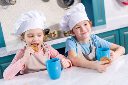 smiling children in chef hats drinking tea and eating cookies in kitchen