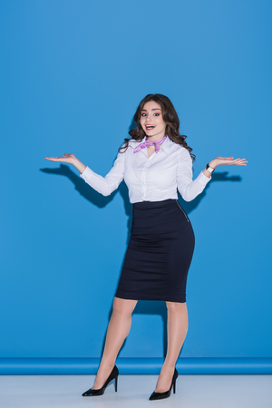 attractive stewardess showing at something with hands on blue