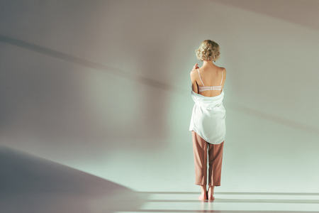 back view of barefoot blonde girl in pink bra, shirt and pants standing in studio on grey