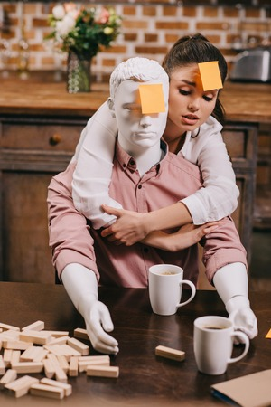 portrait of young woman with sticky note on forehead hugging layman doll, perfect relationship dream concept Zdjęcie Seryjne