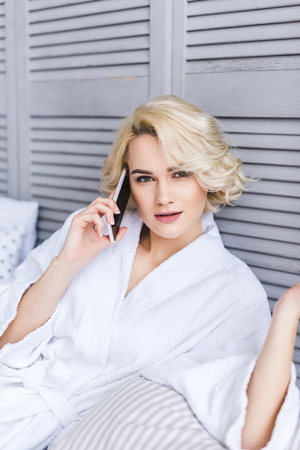 beautiful blonde girl looking at camera while talking by smartphone on bed