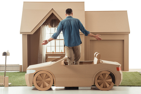 rear view of man in cardboard car in front of cardboard house isolated on white Stockfoto